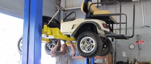 Image of Golf Car mechanic repairing car
